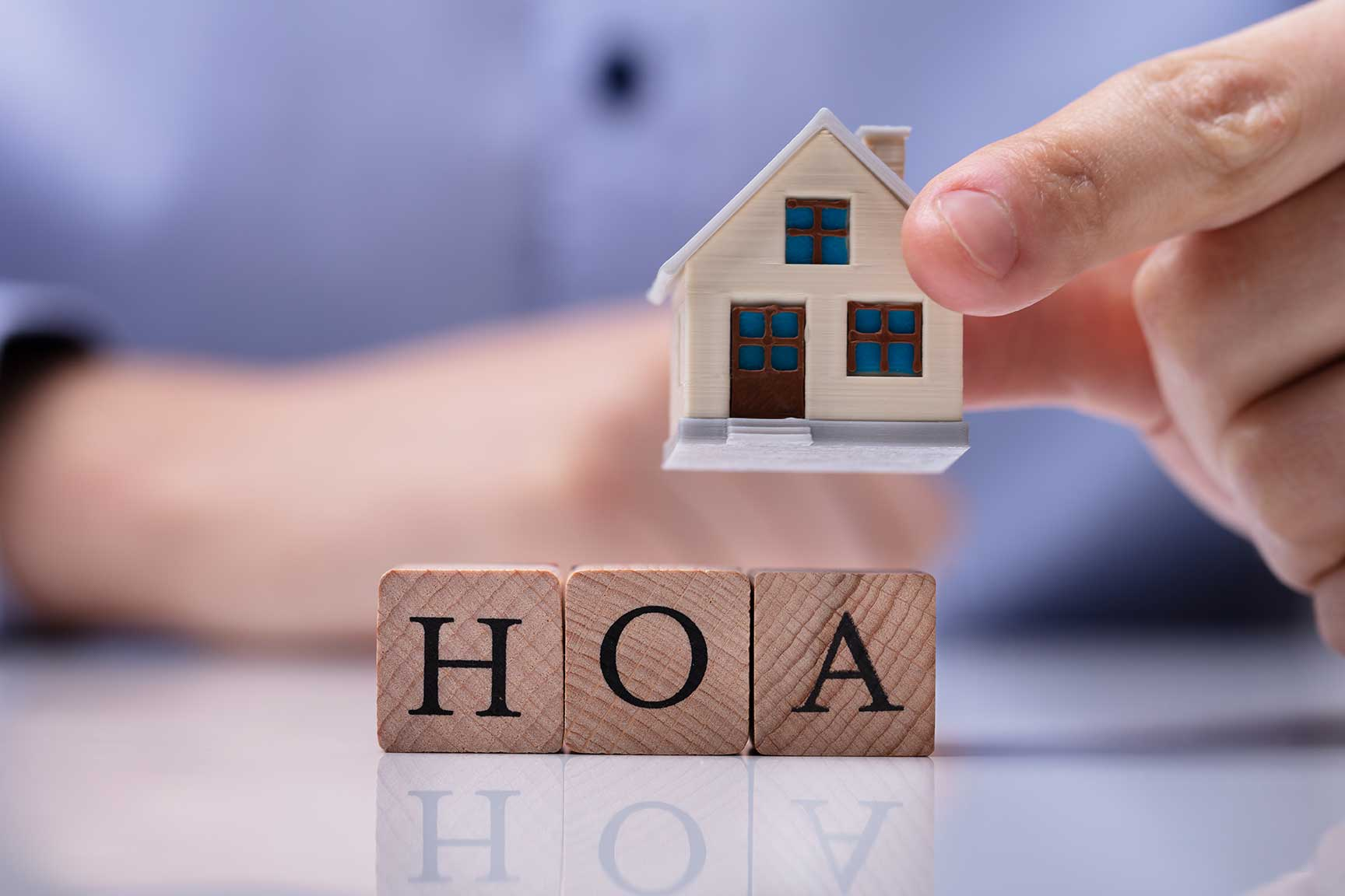 Miniature home with scrabble tiles that read HOA.