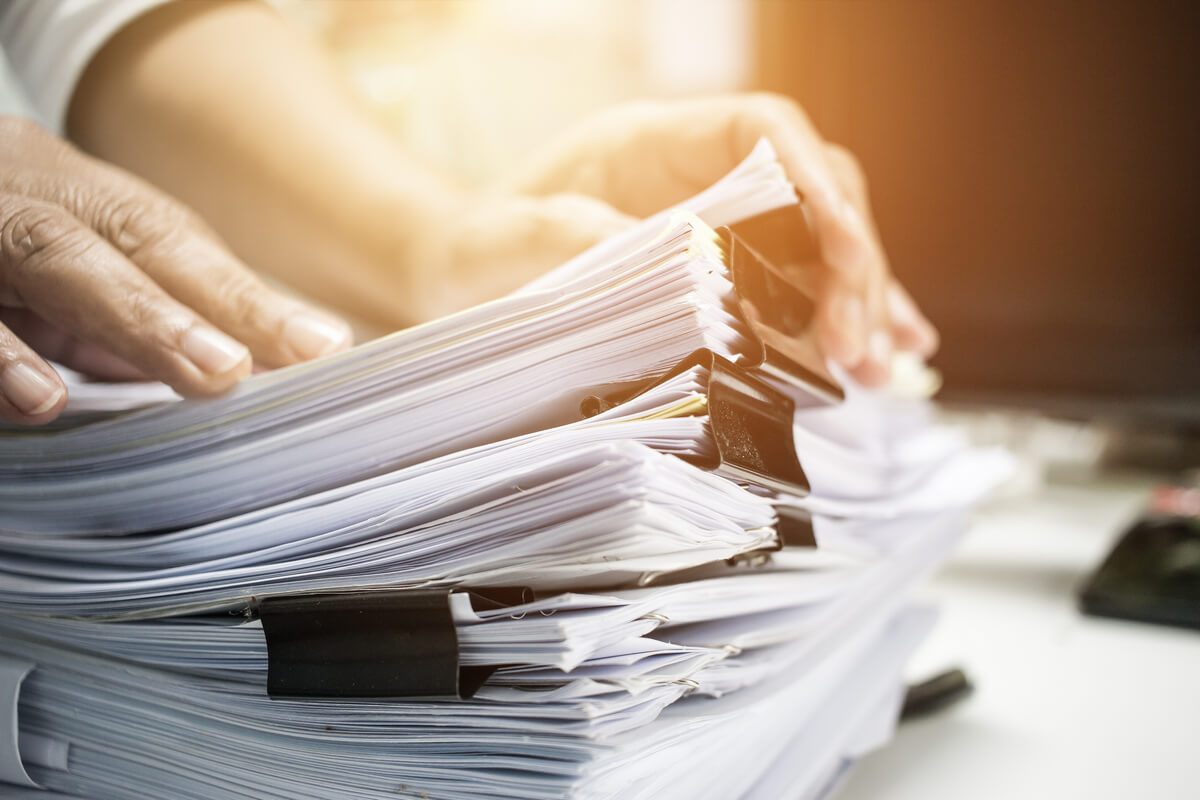 Home buyer sorting through piles of paperwork