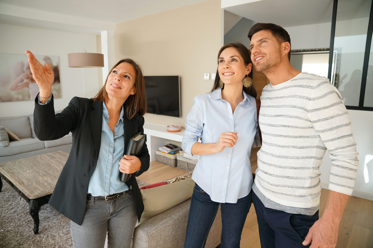 Real estate agent showing a builder's model home to a young couple.